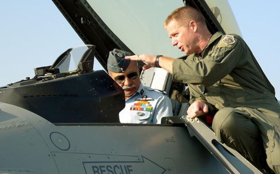 Indian air force General B.C. Nanjapa gets a bird's-eye view sitting in the cockpit of an F-16 at Kalaikunda Air Station, India, as he and Col. Rusty Cabot, U.S. deployed forces commander, discuss the capabilities of the F-16.