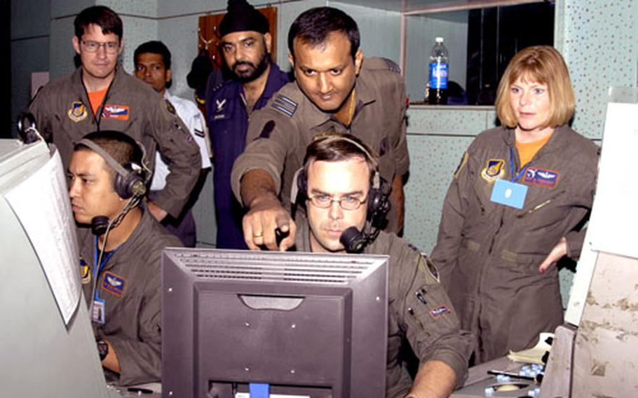 Capt. Michael Thomas, lower center, senior director, and Tech. Sgt. Steven Harshman, lead weapons director, with the 961st Airborne Air Control Squadron from Kadena Air Base, Okinawa, monitor and direct aircraft with an Indian Air Force squadron leader recently during Cope India '06.