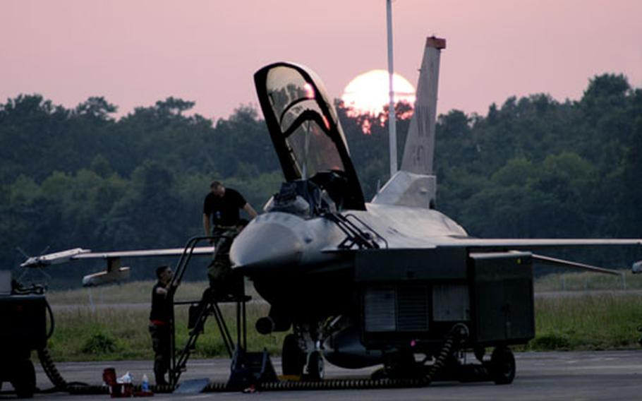 Staff Sgts. Lyle Janey and Allen Conard, along with Sr. Airman Sean Mcelree, all avionics specialists from the 35th Aircraft Maintenance Squadron, Misawa Air Base, Japan, put their finishing touches on an F-16 as the sun sets over Cope India 2006.