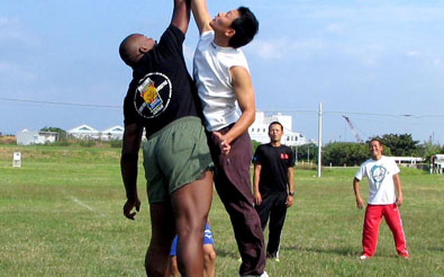 A Marine and a Japanese soldier leap for the ball Tuesday at the opening of a game of dodgeball.