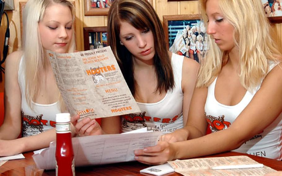German Hooters Girls Chantal Schliepat, Angela Lehmann and Nicole Müller, left to right, brush up on the menu before being tested at the new Hooters restaurant in Neunkirchen, Gremany, on Tuesday.
