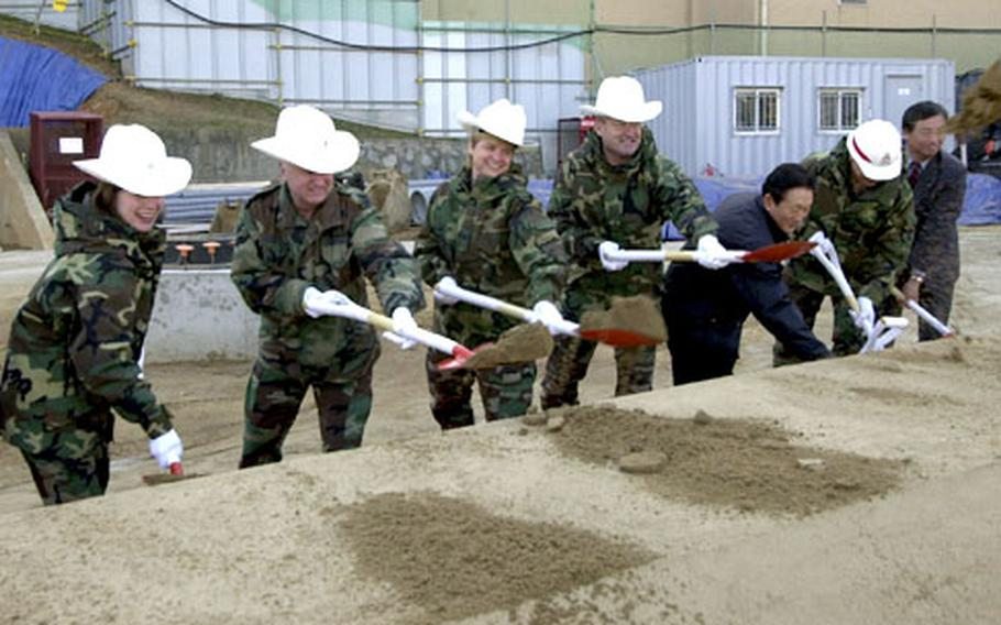 Members of the Osan Air Base community throw the first shovels of dirt during a groundbreaking ceremony for a new housing tower Tuesday morning.