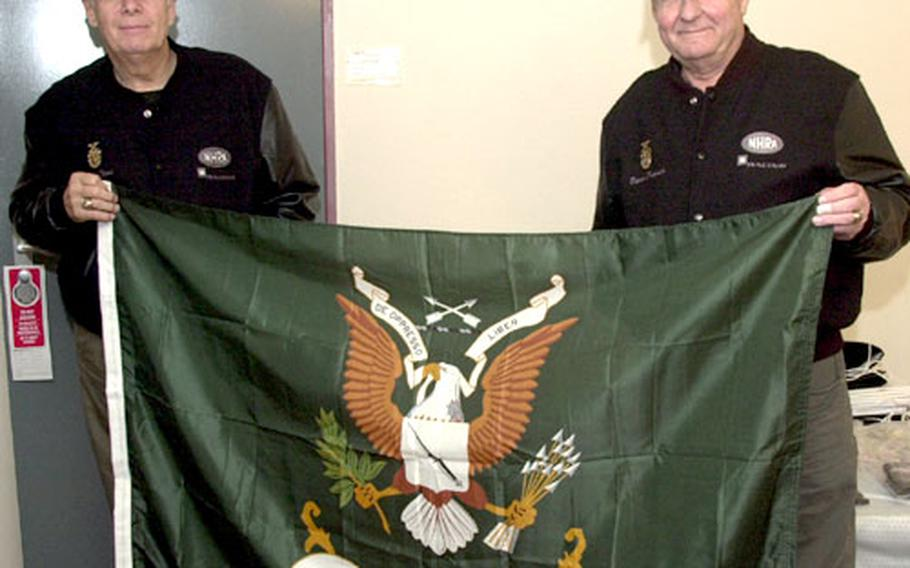 Wayne Reed, left, and Dieter Protsch pose in Reed's Ramstein, Germany, billet with their flag from the U.S. Army Special Forces Association. Reed has made five visits just this year to Landstuhl just to thank soldiers wounded in Iraq and Afghanistan.