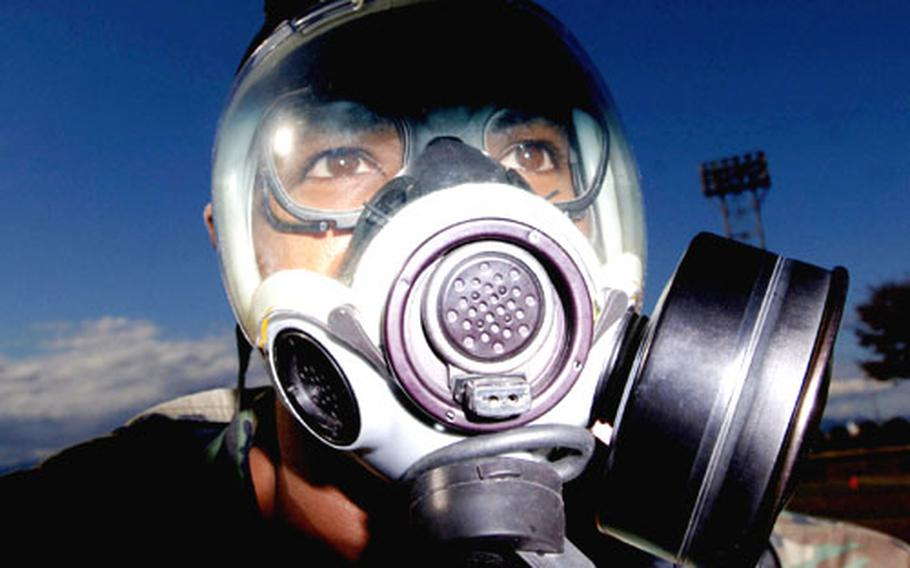 """Tech. Sgt. Quincy Robinson processes through the contaminated control area during """"ability to survive and operate"""" training at Yokota Air Base, Japan. Robinson is a member of the 374th Dental Squadron."""