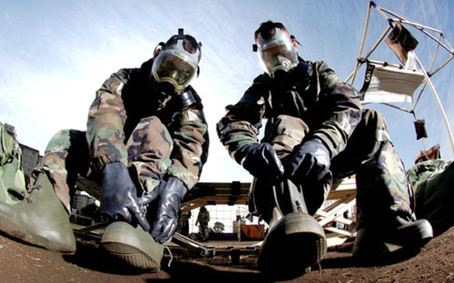 """Staff Sgt. Mark Freeman, left, and Staff Sgt. Tom McCauley remove their protective overboots at the contaminated control area during """"ability to survive and operate"""" training. Both are aerospace ground equipment mechanics from the 374th Maintenance Squadron at Yokota."""
