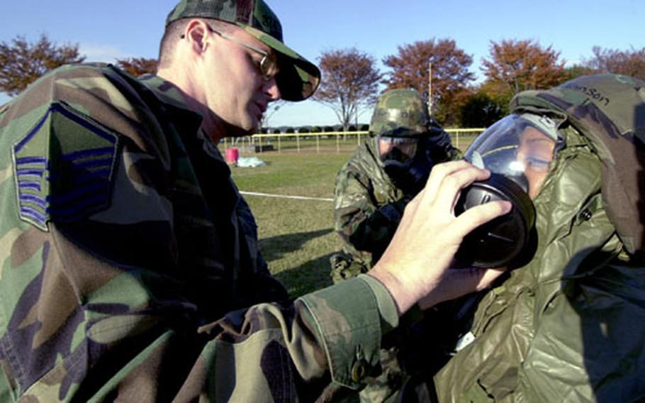 Master Sgt. James Martin instructs airmen on how to check their gear.