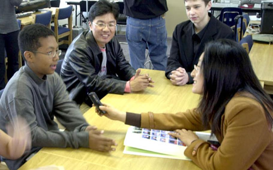 Cho Hyea-ran, a South Korean teacher, interviews pupil and volunteer guide Christopher Campbell, 13, Wednesday at Seoul American Middle School on Yongsan Garrison.