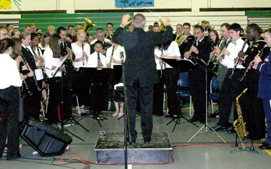 """Naples (Italy) High School band director Gary Marvel conducts the performance of John Philip Sousa's """"The Stars and Stripes Forever"""" Thursday night."""