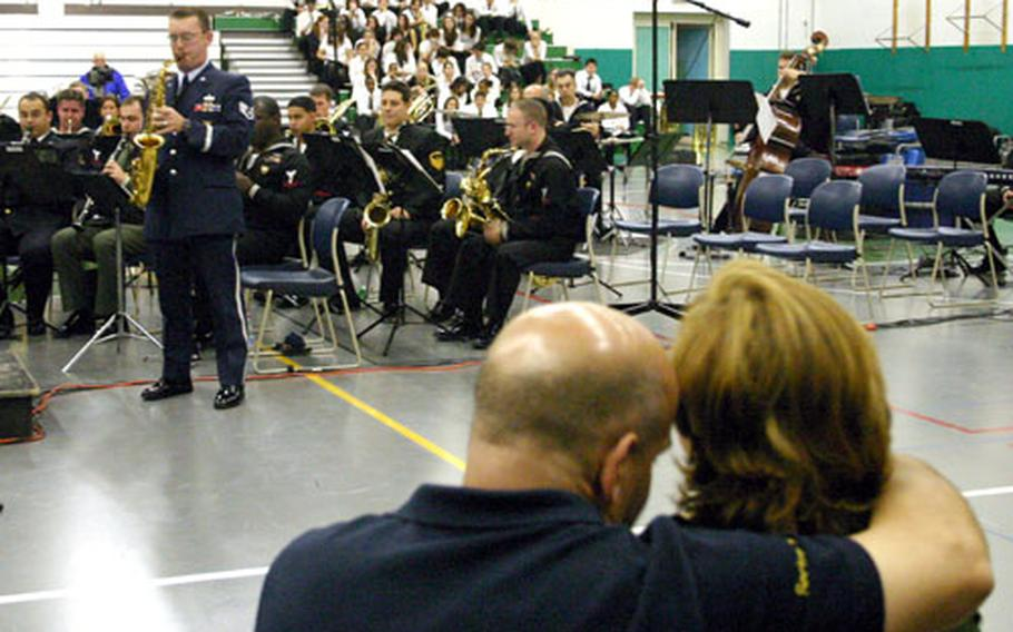 """A couple in the Naples High School gymnasium enjoys Air Force Staff Sgt. Kenneth Drefke's saxophone solo during a rendition of """"A Gershwin Fantasy,"""" arranged by Pat Martino."""