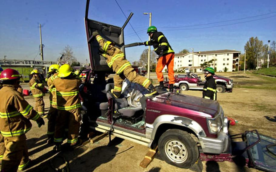 Yongsan Garrison and off-base firefighters peel back the roof of the vehicle.