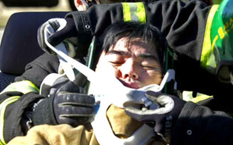 Yongsan Garrison and local firefighters aid the victim in their extraction training.