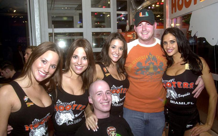 Senior Airman Doug Collins, right, and Air Force Staff Sgt. Edward Mann pose with American Hooters girls Friday at the grand opening party for the Neunkirchen Hooters, the first Hooters to open in Germany.