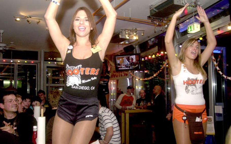 """Hooters girls dance to the Village People's """"YMCA"""" Friday night during the grand opening party for the Neunkirchen Hooters."""