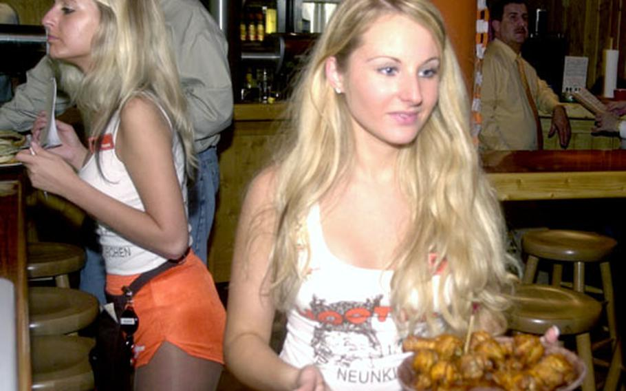 A German Hooters girl delivers a plate of chicken wings Friday night at the grand opening of the Hooters in Neunkirchen, Germany.