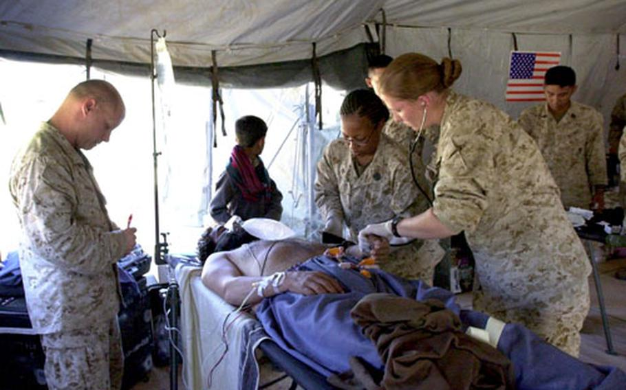 Navy nurses Lt. j.g. Brookes Englebert, right, and Lt. Robert Barrett, left, and Petty Officer 3rd Class Althea Caraballo tend to Muhammad Siab Khan Thursday in their emergency room tent in Shinkiari, Pakistan. Siab Khan was suffering from acute coronary syndrome and was later transferred to a local hospital for further care.