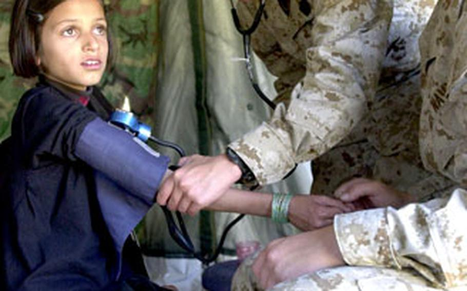 Seaman Lacy Helphenstine, right, watches as Petty Officer 3rd Class Fridalyn Ocampo takes the blood pressure of a young Pakistani girl Thursday in the triage tent of a field hospital from III Marine Expeditionary Force, which has been set up in Shinkiari, Pakistan.