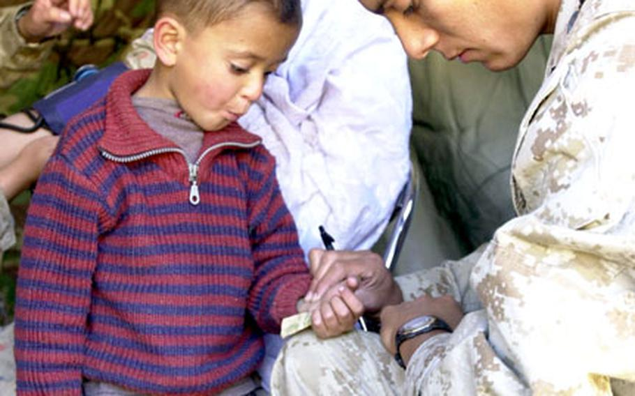 Seaman Garrett Castro, corpsman with 3rd Medical Battalion, checks the pulse of a young Pakistani boy Thursday.