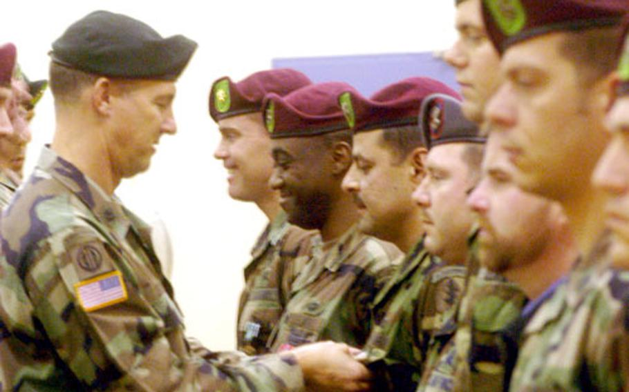 """Lt. Col. John """"Scott"""" Eaddy, left, commander of 1st Battalion, 10th Special Forces Group, pins Bronze Stars and other medals on soldiers from the battalion's Company A, during an awards ceremony Friday at the Panzer Casern gymnasium in Böblingen, Germany."""