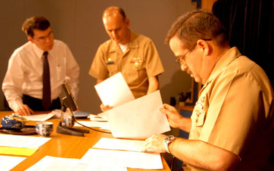 """Last-minute preparations are made by Commander Fleet Activities Yokosuka Master Chief William Holz, right, CFAY Commanding Officer Cpt. Greg Cornish and CFAY spokesman Bill Doughty before """"Commander's Corner"""" goes on the air."""