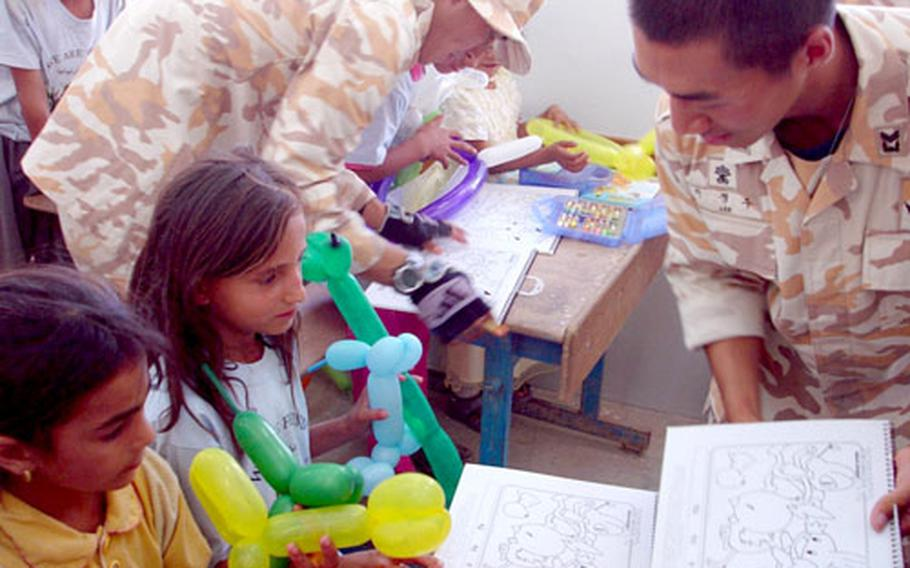 South Korean soldiers show Iraqi schoolchildren coloring books that were among the school supplies they helped distribute to the school. In all, the Taegu American School collected two big boxes of supplies to send to the Iraqi students.