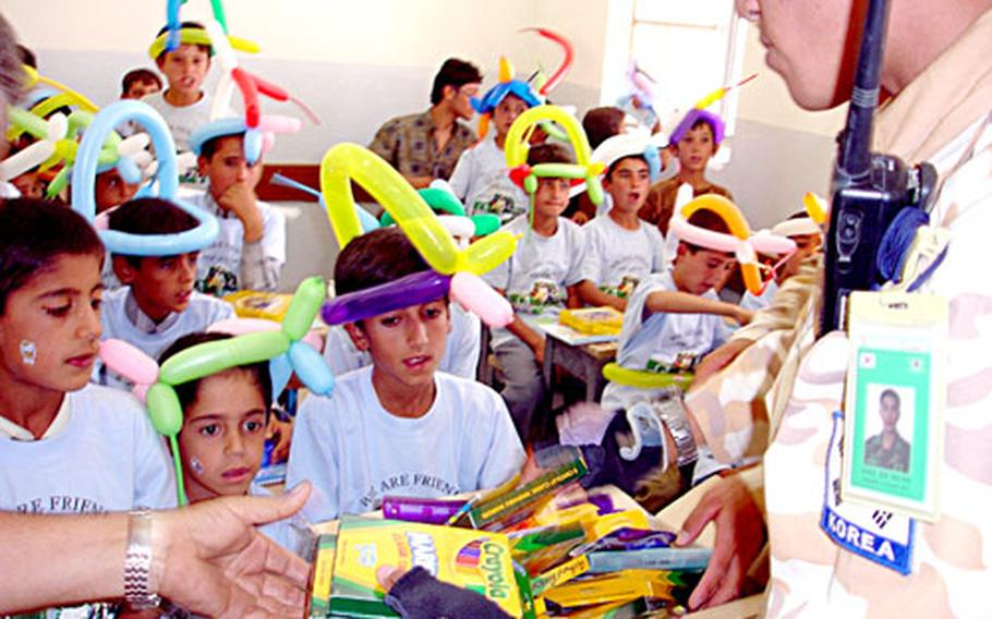 A South Korea Army soldier passes out new boxes of crayons to Iraqi schoolchildren. The crayons were among school supplies collected and donated by children in Taegu American School, Daegu, South Korea, and distributed by U.S. and South Korean soldiers in Iraq.