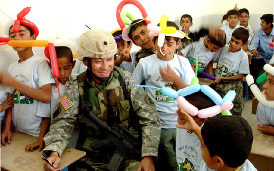 Army Lt. Col Harold Kwon takes some time out to show Iraqi school children the time-honored U.S. custom of making skinny-balloon headgear.