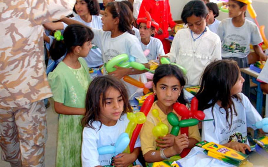 Iraqi school children play with balloons included in school supplies collected and donated by children from Taegu American School.