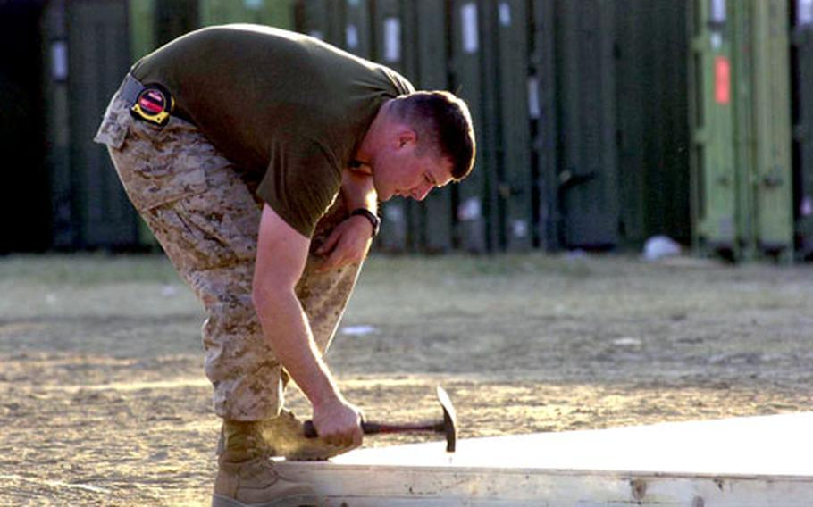 Cpl. Richard Book, a combat engineer with 9th Engineer Support Battalion, puts together a piece of decking in Shinkiari, Pakistan, just hours after arriving at the camp.