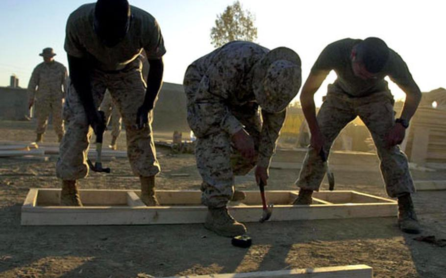 Two Marines and a sailor hammer together a frame to a piece of decking for the III Marine Expeditionary Force's field medical facility in Shinkiari, Pakistan.