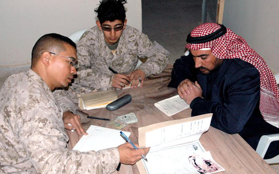 Lt. Col. Robert Glover and a translator meet with an Iraqi man who claims U.S. forces damaged his home and shop during the battle of Husaybah earlier this month.