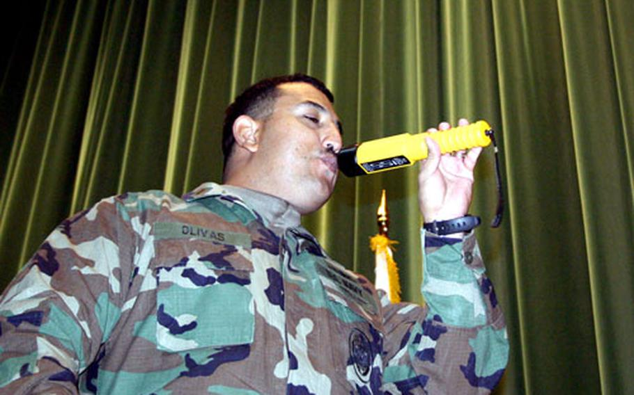 Ensign Shawn Olivas, with security at Naval Support Activity Naples, Italy, demonstrates how security forces can test a driver's blood alcohol level by using the AlcoBlow, a wand that can detect the presence of alcohol on someone's breath and in the air.