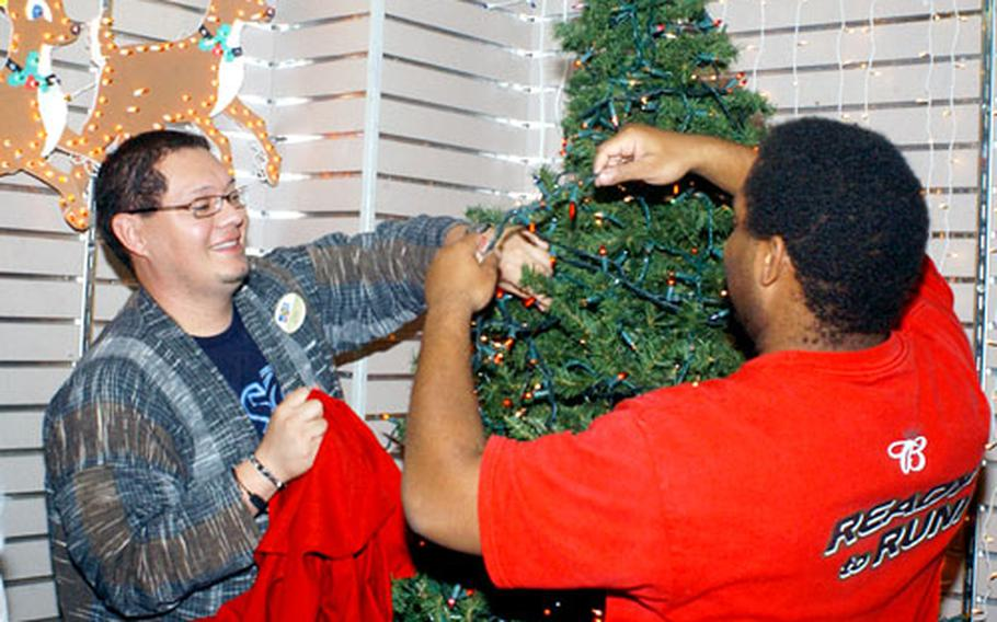 Marine Corps Exchange employees Luis Pena, at left, and Henry B. Rodgers decorate the inside the Marine Corps Air Station Iwakuni store.