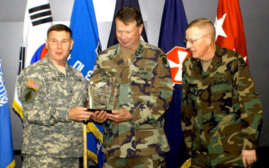 Brig. Gen. Joseph Smith, left, commanding general, United States Army Combat Readiness Center, and director of Army Safety, presents the Army Major Command Safety Award to Lt. Gen. Charles Campbell, 8th Army commanding general with the Chief of Staff, as 8th Army Command Sgt. Maj. Barry Wheeler looks on.