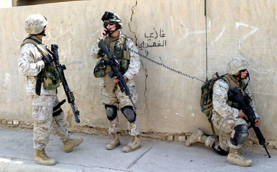 Capt. Christopher J. Bronzi, center, then-commanding officer of Company G, 2nd Battalion, 4th Marine Regiment, speaks with Lt. Col. Paul J. Kennedy, left, battalion commanding officer, as Cpl. Matthew H. Hernandez provides security during a zone-clearing operation in Ar Ramadi, Iraq.
