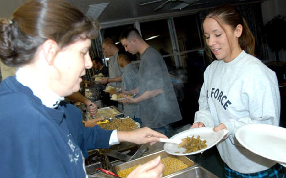 Lt. Col. Cheryl Kearney, 373rd Intelligence Group commander, serves Airman 1st Class Jennifer Bratten some green beans and corn during the annual Thanksgiving dorm feed, which was served to about 300 unaccompanied personnel assigned to the 373rd Intelligence Group.
