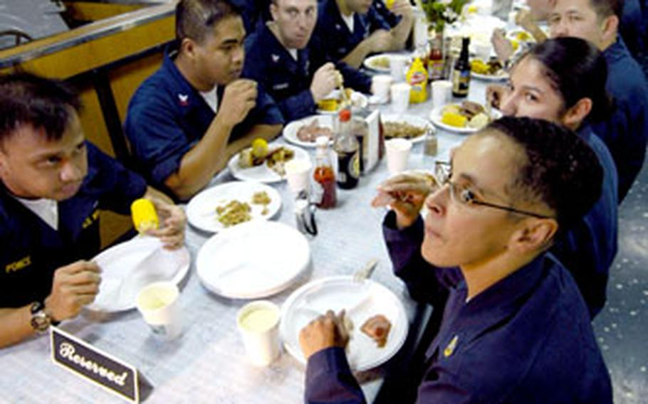 USS Kitty Hawk sailors partake in a Thanksgiving meal that included more than 6,000 pounds of food prepared in 30 menu items.