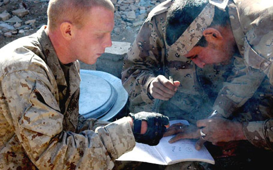 Lance Cpl. Christopher Thomas seeks help with his Arabic Language studies from an Iraqi Army soldier in Husaybah.