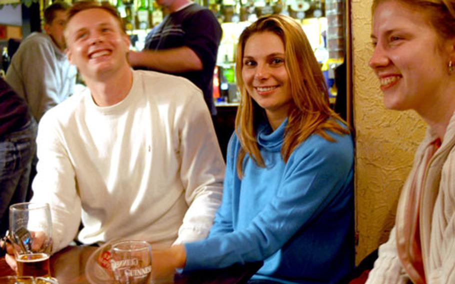 Czech Republic natives, left to right, Petr Zemek, Mirka Krockova and Petra Dudova enjoy a drink as business hours wind down at The Locomotive pub in Cambridge recently. The pub, like most in England, closed at 11 p.m., but starting Thursday it will be open until 2 a.m. on weekends.