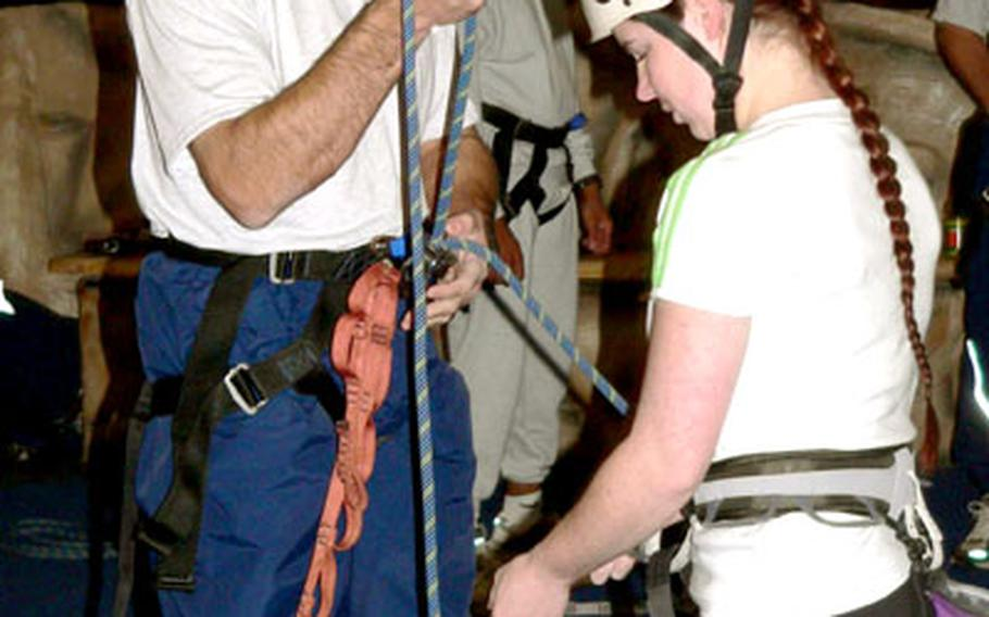 Staff Sgt. Christine Mahler, an experienced rock climber and volunteer, shows Col. Sam Angelella, 35th Fighter Wing commander, the proper technique for belaying a climber at the Weasel's Den during Wingman Day at Misawa Air Base, Japan, on Wednesday.