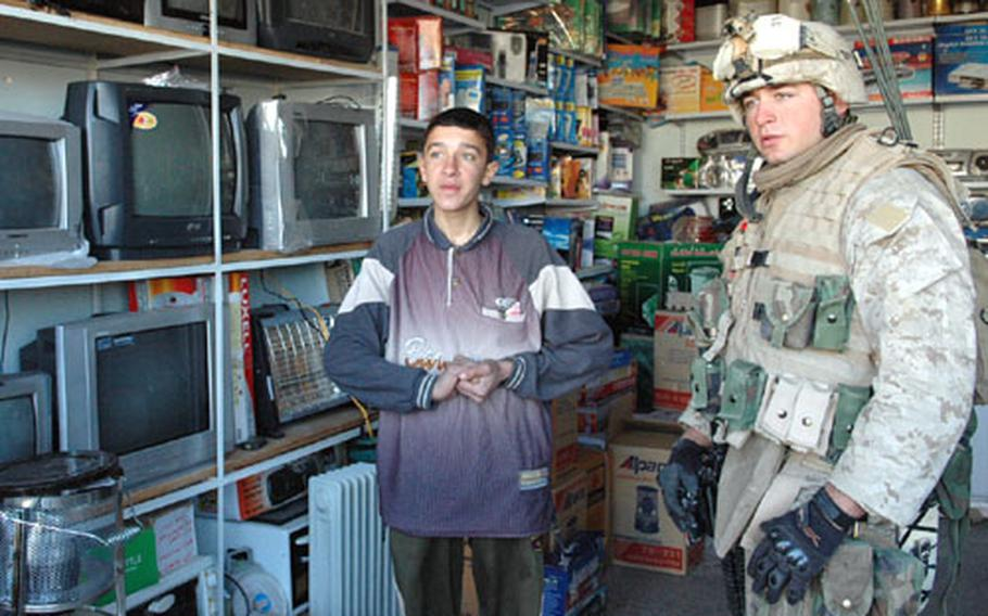 Lance Cpl. Michael Virts consults with an Iraqi store clerk about the television Virts' platoon pooled money to buy.