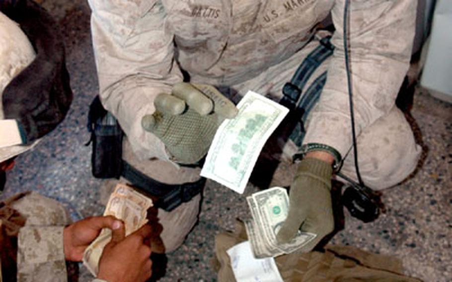 Cpl. Jeff Gattis offers up a mixture of U.S. dollars and Iraqi dinars to buy a television, satellite dish and receiver — a $230 package.