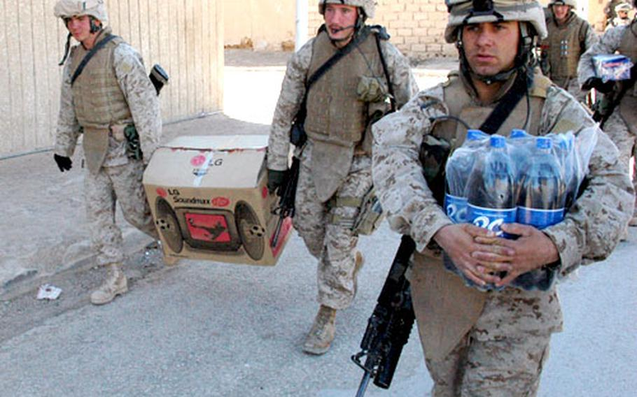 Lance Cpl. Kyle Woodbine, left, and Cpl. Joseph Walker carry their platoon's newly-purchased television down a side street of Husaybah, while Cpl. David Rios carries a six-pack of soda.