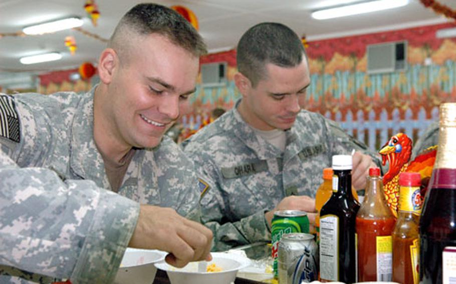 Spec. Timothy Sprague and Sgt. Morgan O'Hara of Company A, 3rd Battalion, 3rd Brigade, 101st Airborne Division, enjoy a Thanksgiving meal at the Camp Union dining facility in Baghdad's Green Zone.