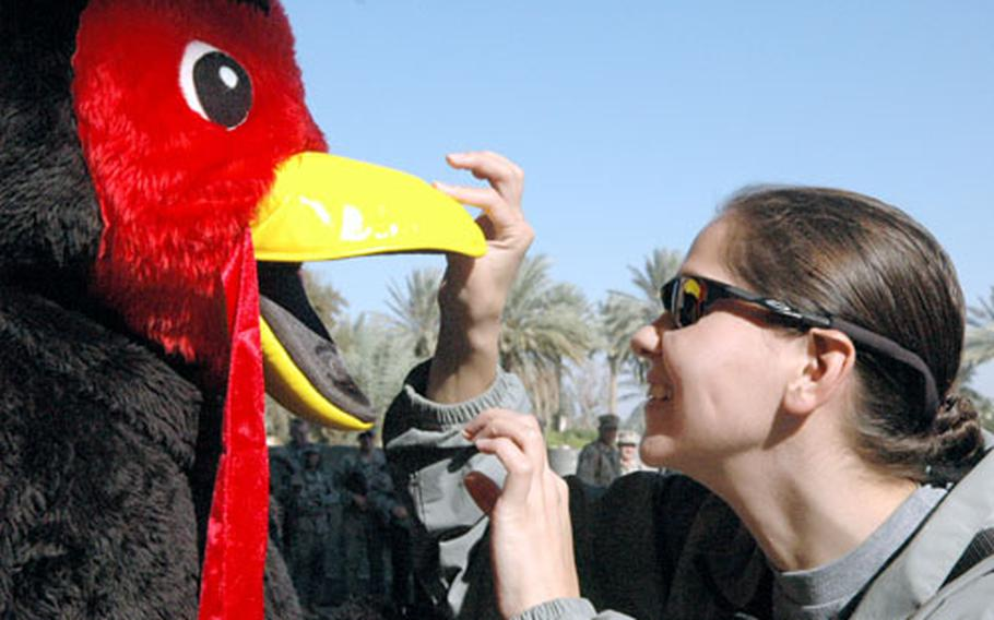 First Lt. Amanda Metz, of Bravo Company, 4-3 Brigade Troops Battalion, 3rd Infantry Division, peers into the turkey costume of Spc. Douglas Favor, Forward Support Company, 4th Battalion of the 64th Armor Regiment, attached to the 3rd Infantry Division at Camp Prosperity in Baghdad's Green Zone on Thursday.