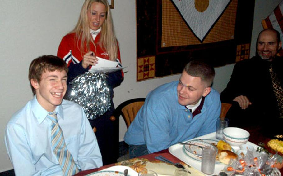 Neill Warrington, left, and his brother, Spc. Soren Hultman of the Hanau, Germany-based 127th Aviation Support Battalion, receive autographs from New England Patriots cheerleader Cara Orazietti on Thursday during a Thanksgiving lunch at Landstuhl Regional Medical Center. Four of the cheerleaders from the Super Bowl champions visited Landstuhl as part of a tour with musicians Trick Pony and John Popper.