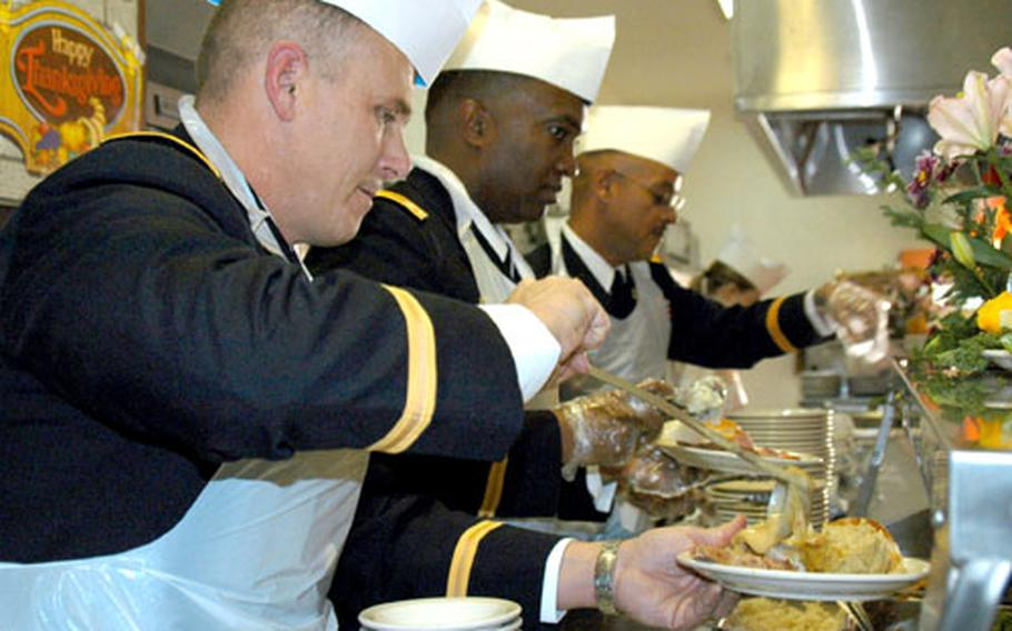 Lt. Col. Steve Bunch, with the 8th Army's Headquarters and Headquarters Company, ladles gravy onto a Thanksgiving dinner at the Three Kingdoms Inn on Yongsan Garrison. It's an Army tradition for officers and senior NCOs to serve a Thanksgiving meal to their troops.