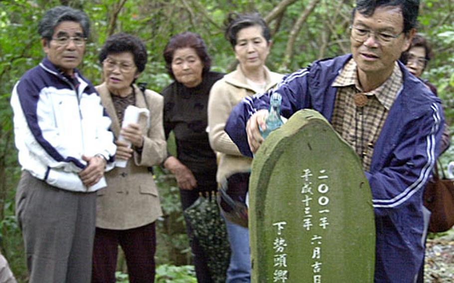 Takashi Hanashiro, 68, a former high school principal, pours sake over a shrine honoring Okinawan ancestors Wednesday in a jungle area near Chula Vista housing on Kadena Air Base. Kadena officials invite dozens of locals to visit sacred ancestral sites located on base several times each year.