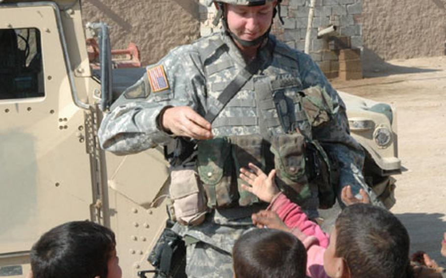Pvt. Mark Johnson, 23, hands out candy and treats in a village near Hawija, Iraq.