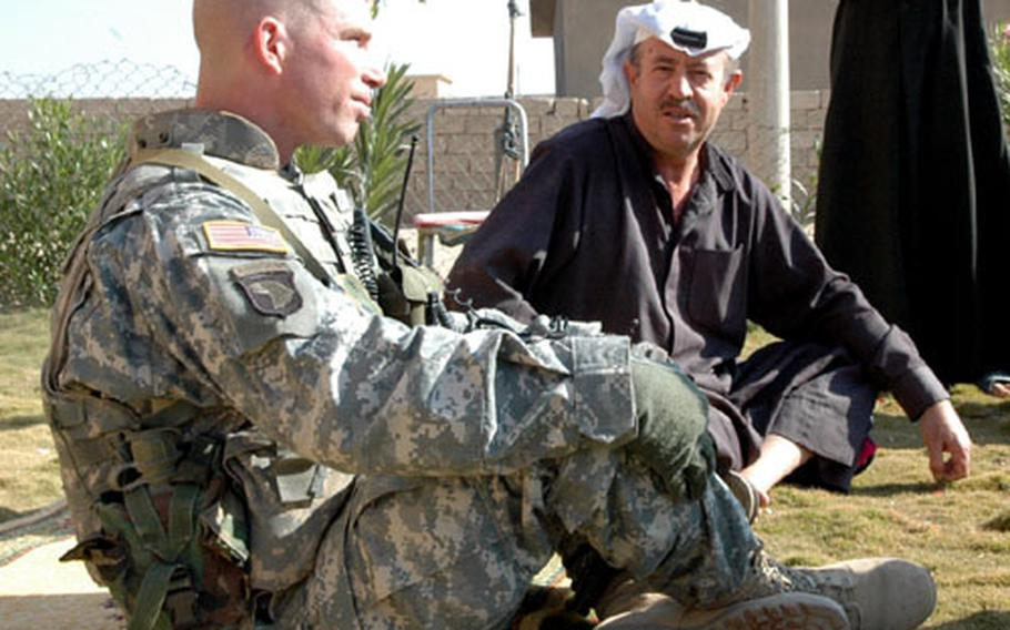 Abu Al Jeiss village leader Faik Ibrahim sits with 2nd Lt. Mike Frank. Ibrahim said he has seen improvements since American forces first came to the area in 2003.