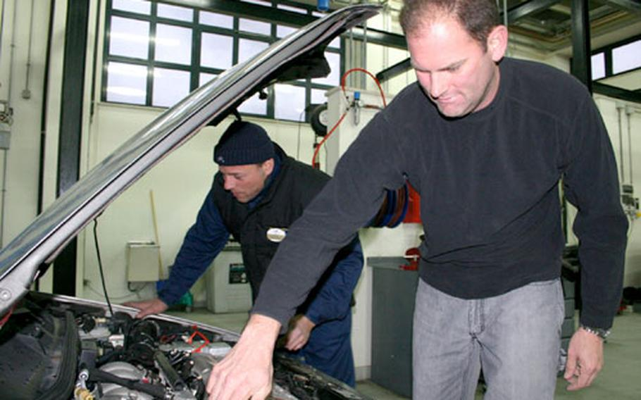 Chief Petty Officer John Whitley, foreground, checks the antifreeze level in his vehicle Tuesday while Massimo Quartucci, who works at the Auto Skills Center at Naval Support Activity Naples, Italy, checks over the engine's hoses and belts. Whitley visited the center this week to winterize his car.